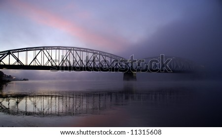 The bridge in foggy sunrise with reflection in water
