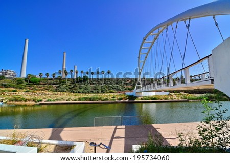 The Bridge of Strings in Hadera Stream Water Park with the Orot Rabin (formerly Maor David) power plant in Hadera, Israel - super wide angle view