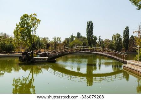 The bridge on the lake in city park in Yerevan - stock photo