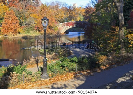 The bridge over the Central Park Pond surrounded by Autumn splendor in New York City - stock photo