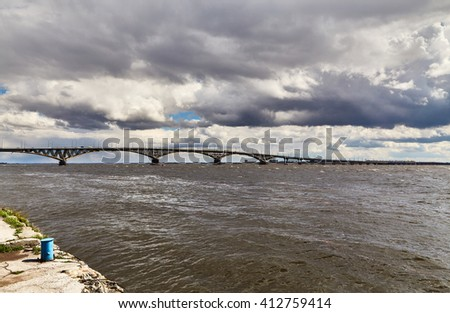 The bridge through the Volga River and the sky with clouds. Strong wind, storm.