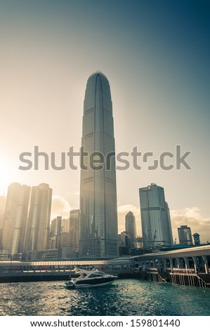 The bright afternoon sunlight shines behind the skyscrapers of Hong Kong, while a yacht drifts along Victoria Harbor. - stock photo