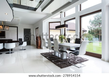 The bright dining room connected to the kitchen in the residence - stock photo