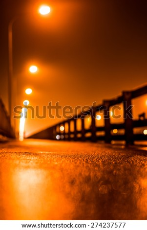 The bright lights of the city at night, walk across the bridge. View from ground level