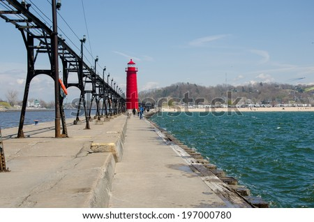 The bright red lighthouse by the Grand Haven beach - stock photo