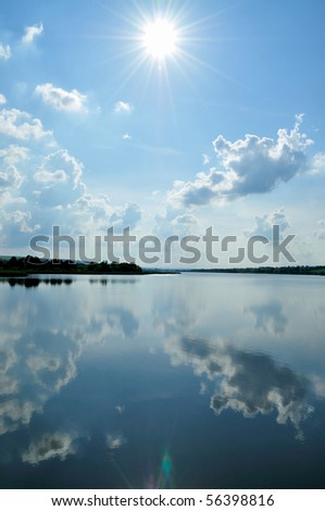 The bright sun with the clouds reflected in water