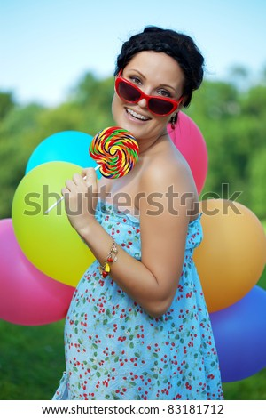 The bright woman in sunglasses with balloons and candy - stock photo