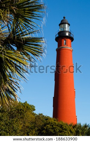 The brilliant red lighthouse at Florida's Ponce de Leon Inlet (formerly Mosquito Inlet) has stood watch over the Atlantic Ocean since 1887 and is the tallest in the state. - stock photo