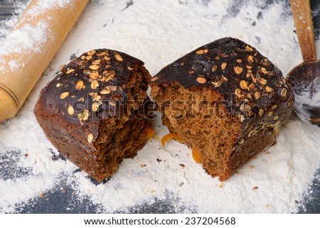 the broken black bread with flour on the table - stock photo