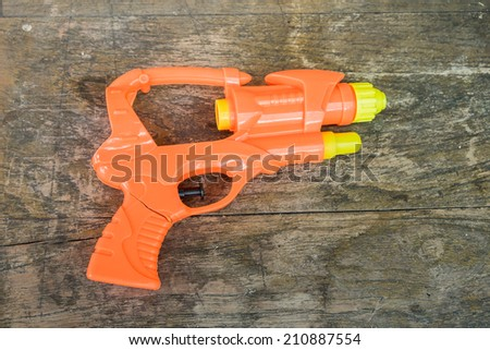 The broken toy gun on the wood background  - stock photo