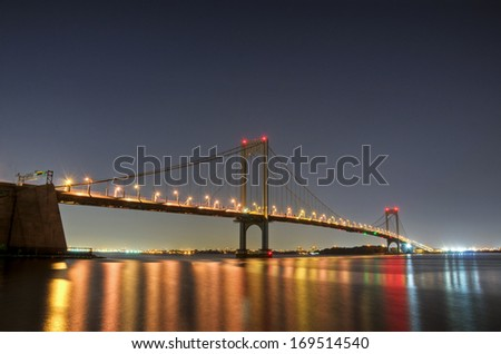 The Bronx-Whitestone Bridge reflecting on the East River at night in New York.