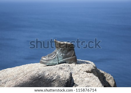 The bronze boot of Cape Finisterre, Spain marks the end of the pilgrimage and the pilgrims who have successfully completed the route of the Camino de Santiago. Here they burn their boots and clothes. - stock photo