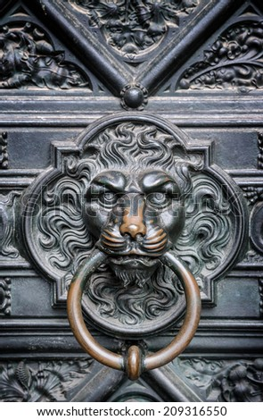The bronze knocker in the shape of a lion head from the gate of the Cologne Cathedral in Germany  - stock photo