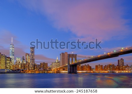 The Brooklyn Bridge at dusk and sundown spanning across the east river between Brooklyn and lower Manhattan and the Financial district
