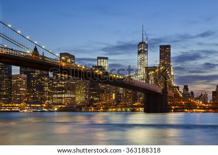 The Brooklyn Bridge in front of the Manhattan skyline in New York City at night. - stock photo