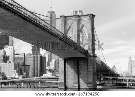 The Brooklyn Bridge is one of the oldest suspension bridges in the United States. Completed in 1883, it connects the New York City boroughs of Manhattan and Brooklyn by spanning the East River. - stock photo