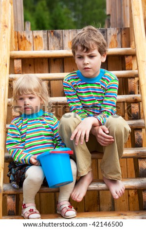 The brother and sister on a children's playground in identical clothes - stock photo