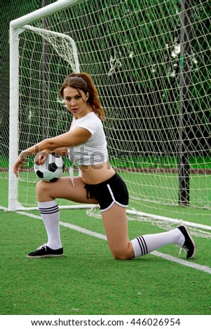The brunette young woman in soccer suit play on the field with black and white ball