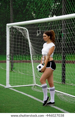 The brunette young woman in soccer suit plays on the field with black and white ball