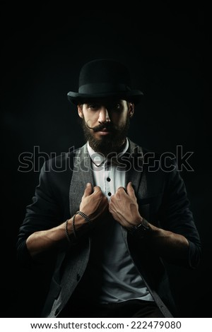 The brutal bearded man in a black bowler hat holding his lapels - stock photo