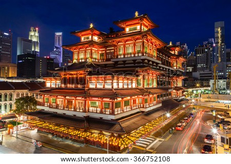 The Buddha Tooth Relic Temple comes alive at night in Singapore Chinatown, with the city skyline in the background. The temple is brightly lit in preparation for Chinese New Year. - stock photo