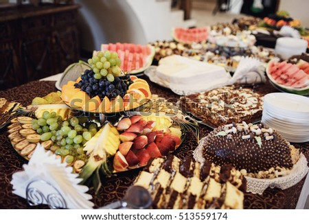 The buffet table with cakes and fruits