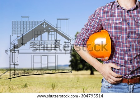 the builder hold  a helmet in his hand, outdoors.