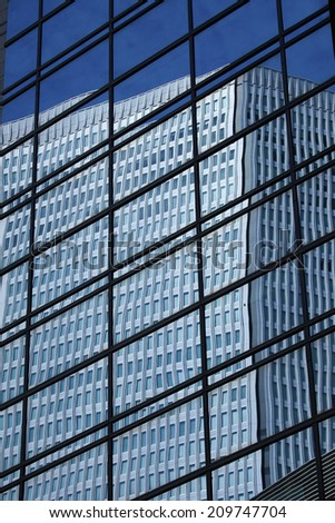 The Building Reflected In The Glass Windows Of A Building - stock photo