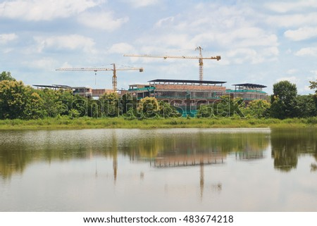The Building Under Construction with The Two Crane inside The Reservoir