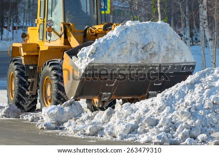 The bulldozer cleans from the road old snow - stock photo
