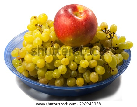 the bunch of grapes and an Apple lying on the plate - stock photo