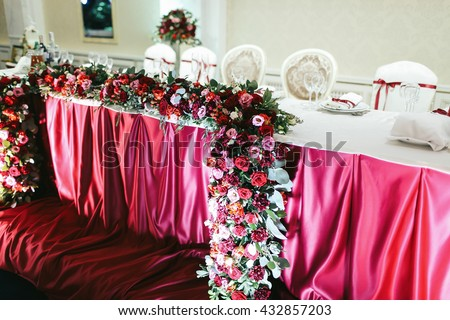 The bunch of red roses, pionies and ranunculus as a part of wedding table decoration