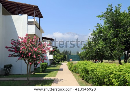 The bungalows along the alley with tangerine trees. Turkey, Kemer. - stock photo