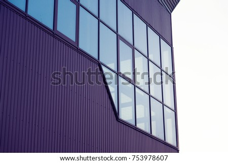 The burgundy building with windows on the sky background