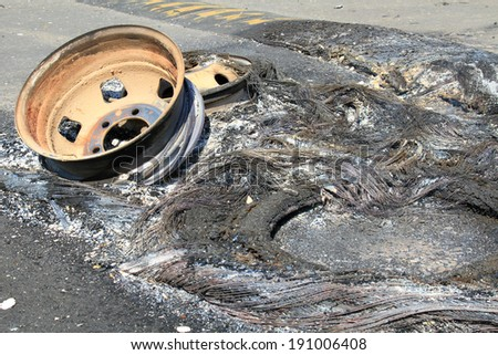 the burned-down bus wheel on the road - stock photo