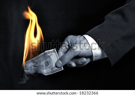 The burning dollar in a hand - stock photo