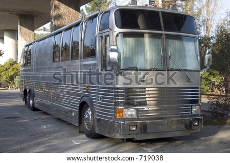 The bus for a rock band hides below a freeway overpass. - stock photo