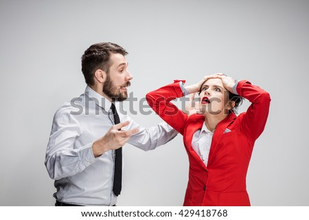 The business man and woman conflicting on a gray background