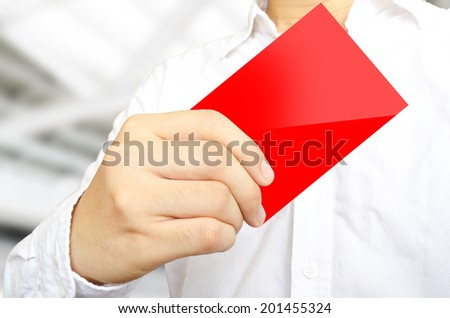 The business man in white shirt is showing the red card on blur office background - stock photo