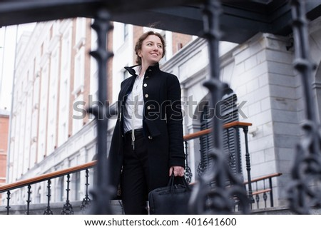 the business woman with a bag for the notebook stands on a ladder against urban city background