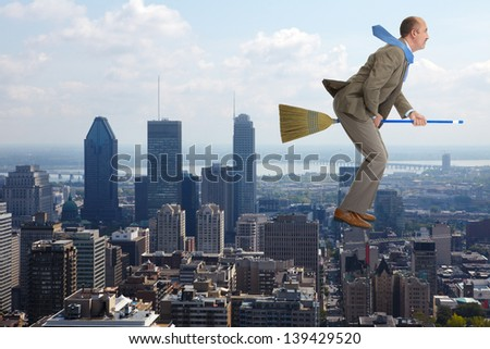 The businessman flies over air on a broom - stock photo