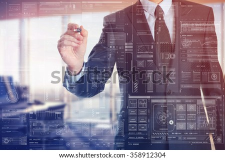 the businessman in the office is writing on the transparent board  - stock photo