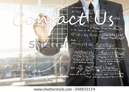 the businessman in the office is writing on the transparent board: Contact Us - stock photo