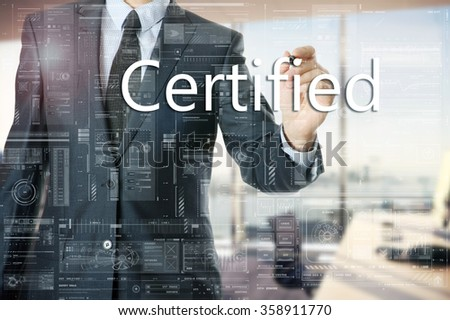 the businessman in the office is writing on the transparent board words associated with the manufacturing: Certified - stock photo