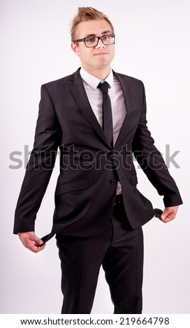 The businessman in the suit shows his empty pockets on a gray background - stock photo