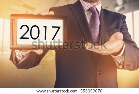 The businessman is presenting the chosen subject concerning the 2017 on the tablet