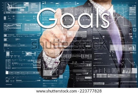 the businessman is pressing the button on the touch screen: Goals , business concept describing the modern business  - stock photo