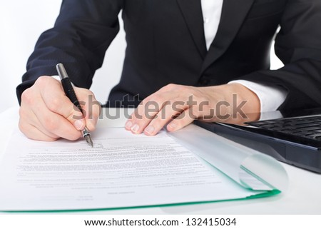 The businessman is signing on the papers - stock photo