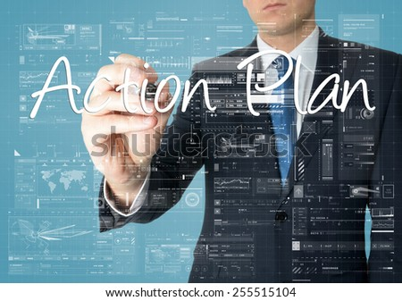 the businessman is writing Action Plan on the transparent board with some diagrams and infocharts - stock photo