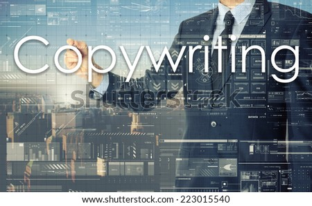 the businessman is writing Copywriting on the transparent board with some diagrams and infocharts with the city in the background - stock photo